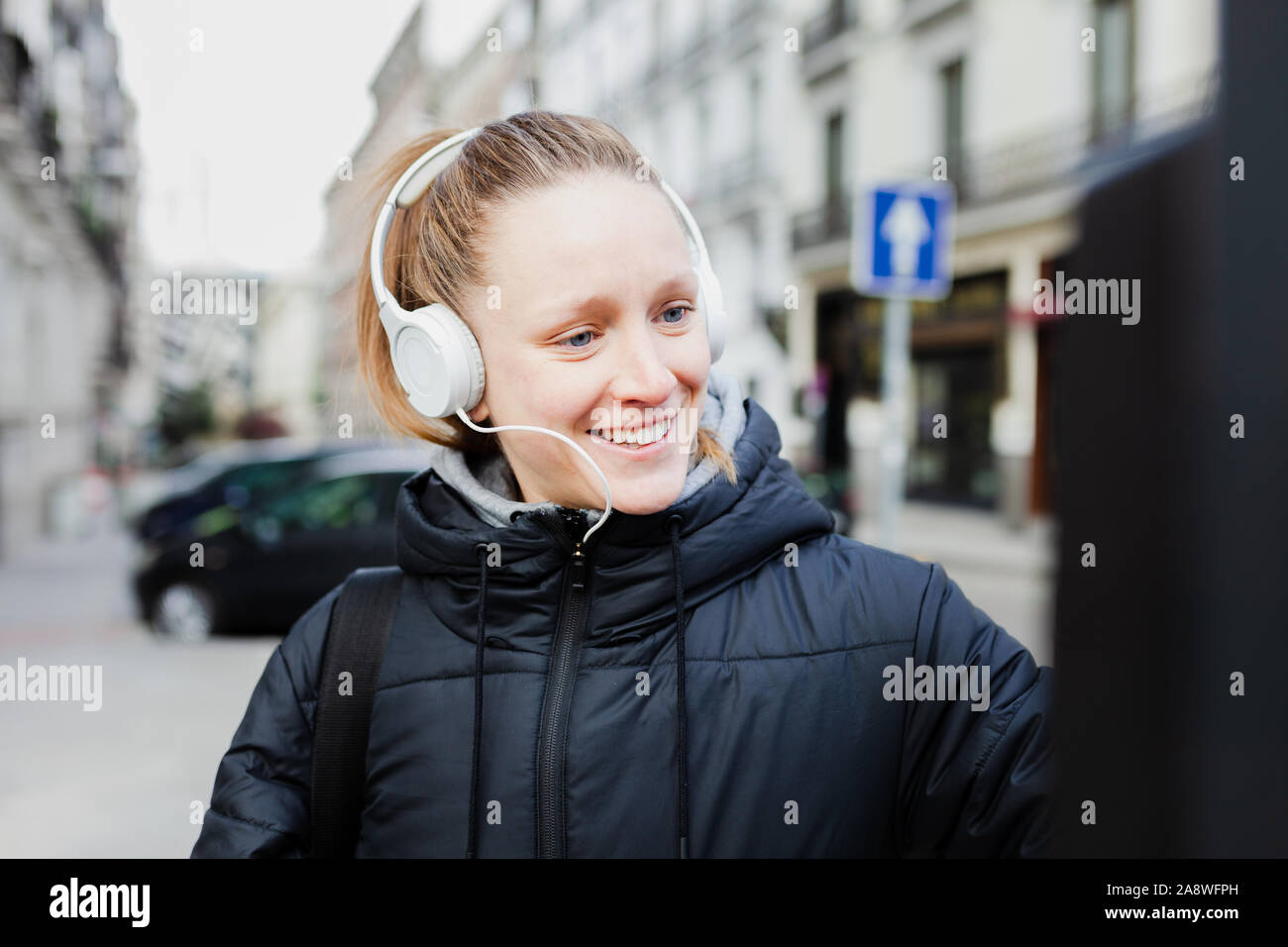 Young blonde woman paying on parking meter in the city with surprised face wearing a jacket an headphones Stock Photo