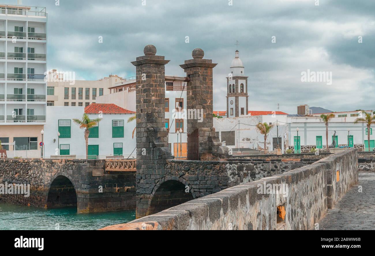 Puente de las Bolas (Bridge of the Balls) is old draw bridge connecting  the centre of  Arrecife city  with Castle of San Gabriel. Stock Photo