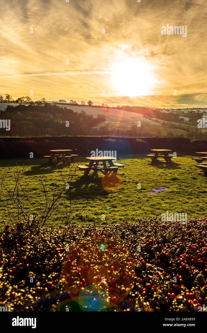 Sunset over some picnic tables in the glorious Derbyshire peak district national park, Empty tables on a frosty cold January evening at sunset Stock Photo
