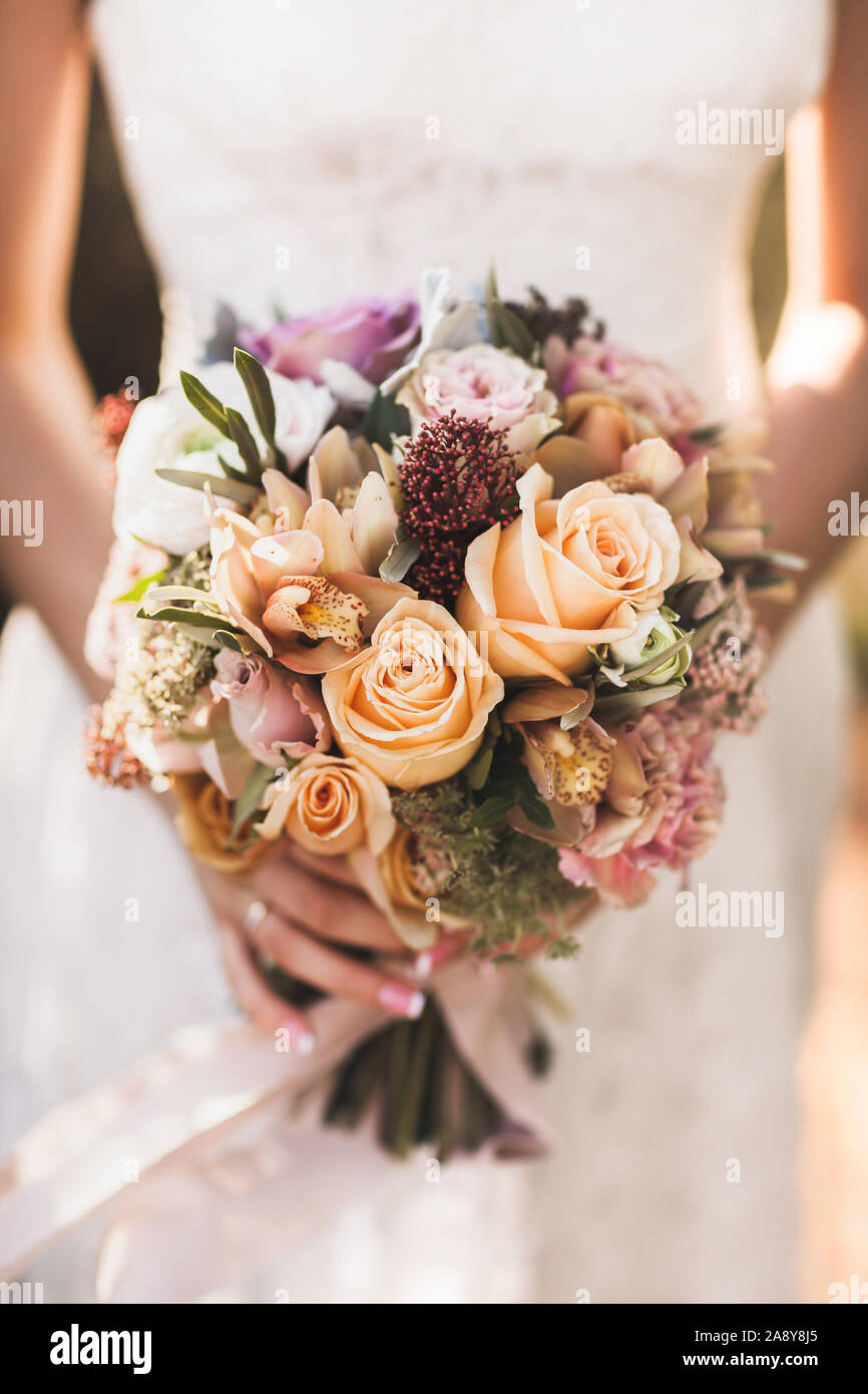 Bride Holding In Hands Small Wedding Bouquet In Orange Autumn Colors Pink And Orange Roses White Peony Dried Flowers And Leaves Stock Photo Alamy
