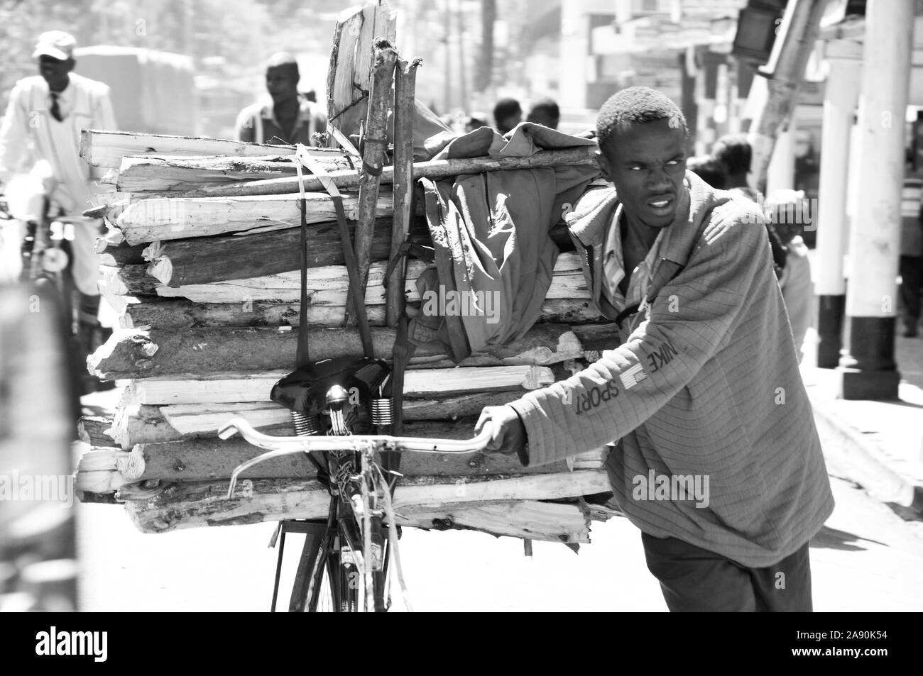 Rift Valley: A young man carring wood on his bycicle trough the streets of Eldoret city Stock Photo