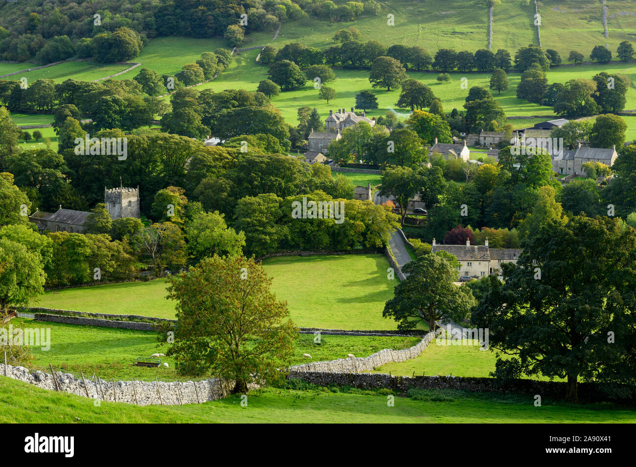 Summer evening sunlight on picturesque Dales village (church & houses) nestling in valley under upland hills - Arncliffe, North Yorkshire, England, UK Stock Photo