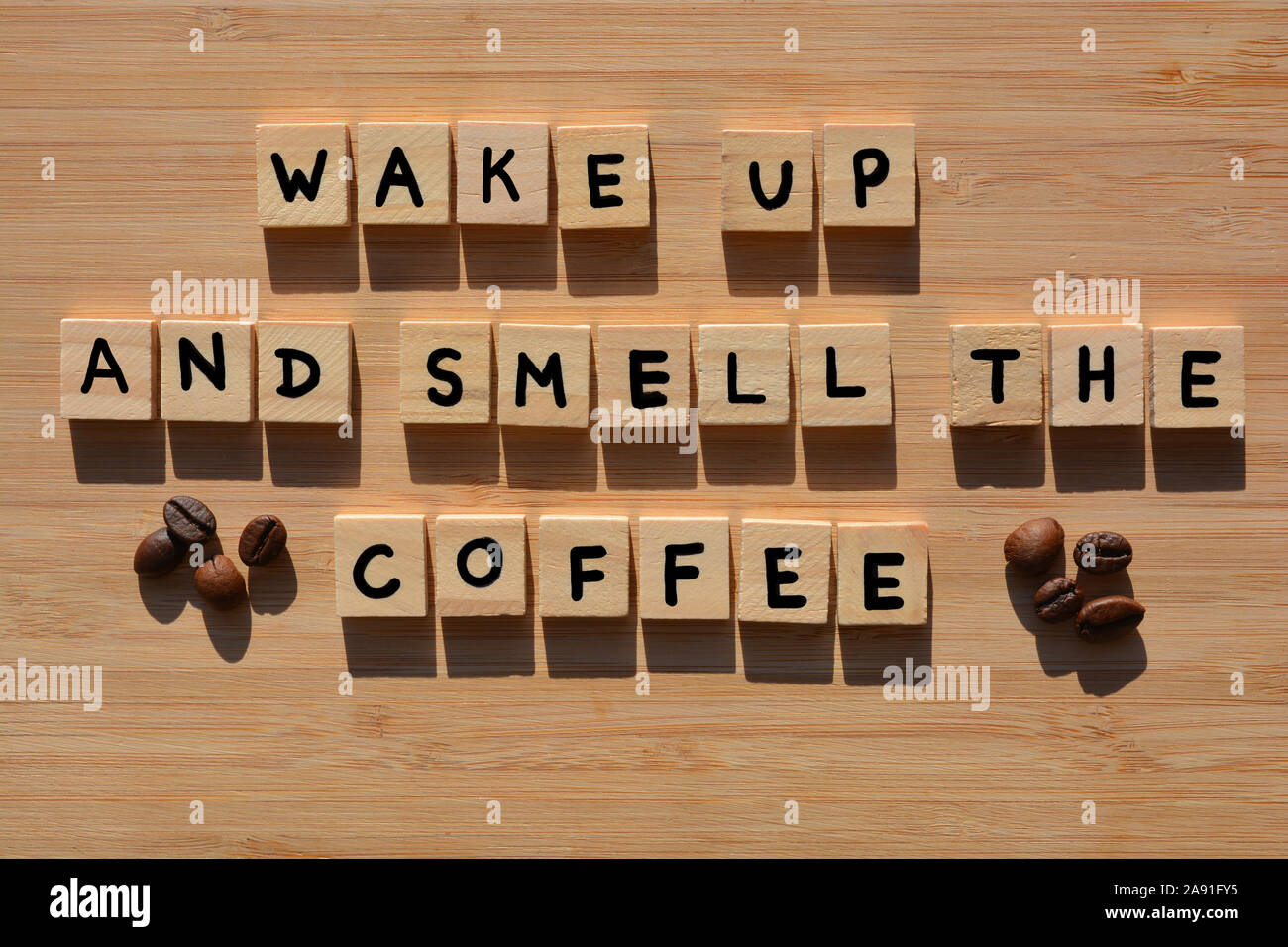 Wake Up And Smell The Coffee in 3D wooden alphabet letters with roasted coffee beans on a bamboo wood background Stock Photo