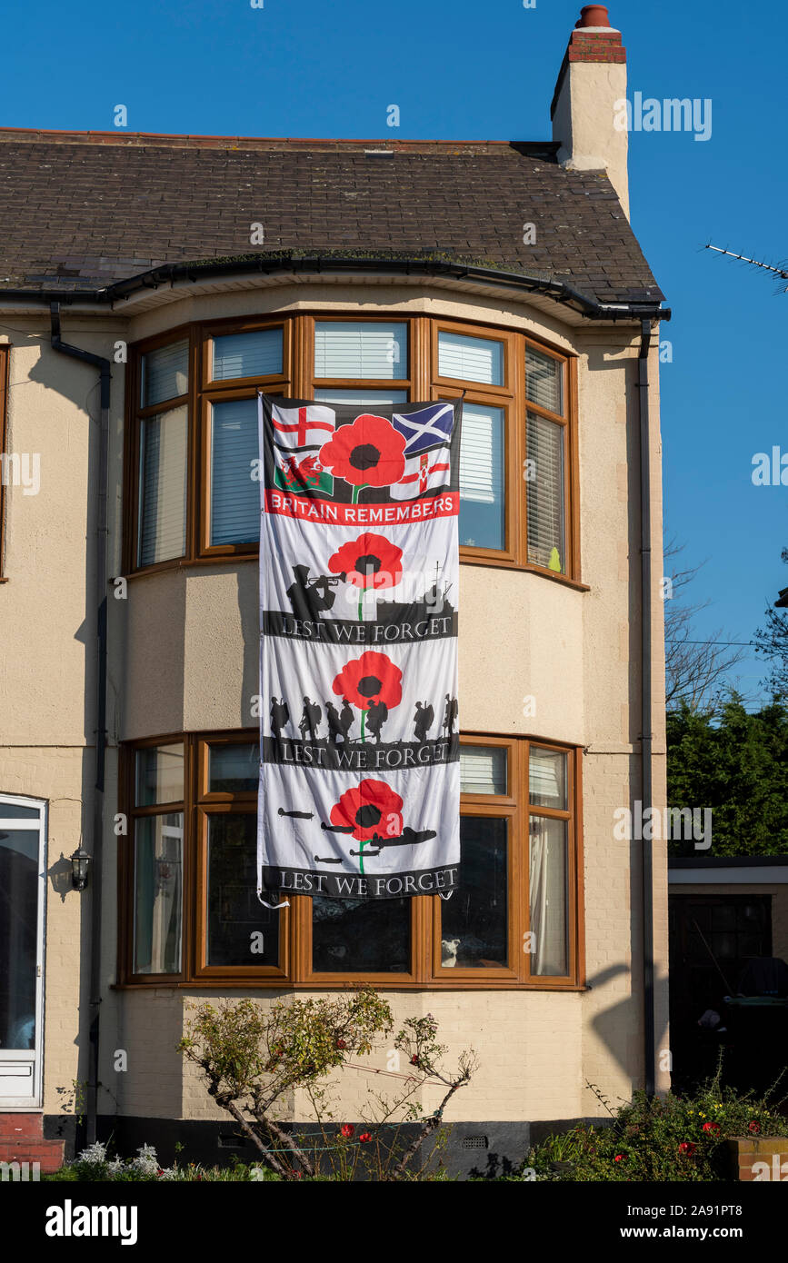 Large Lest we forget flag banner hanging from house on Remembrance Sunday in Southend on Sea, Essex, UK. Home, remembering Stock Photo
