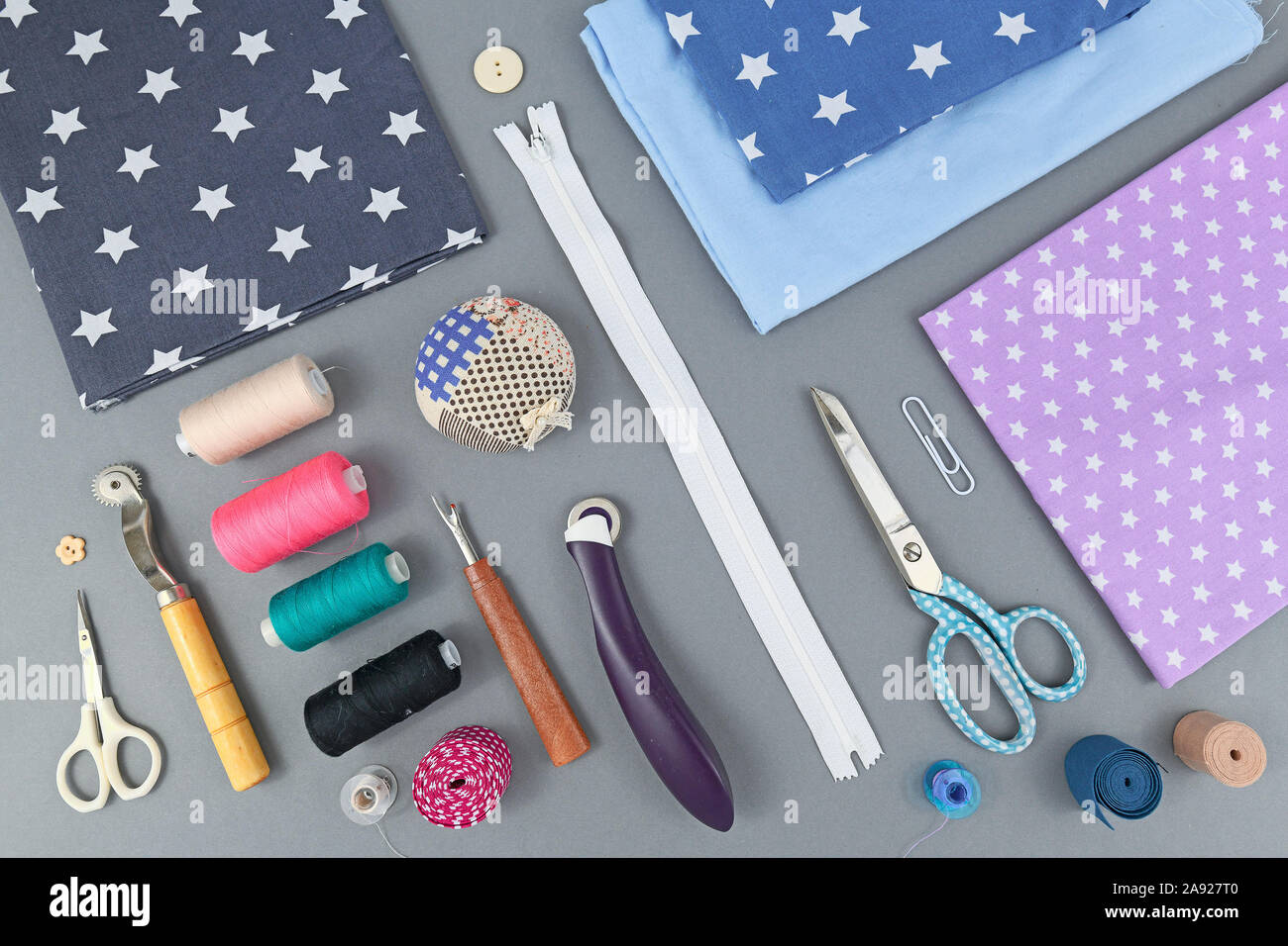 Overhead flat lay with various different sewing tools like fabric, thread, zipper, scissors, spool, thread seperator, pincushion or rotary cutter on g Stock Photo