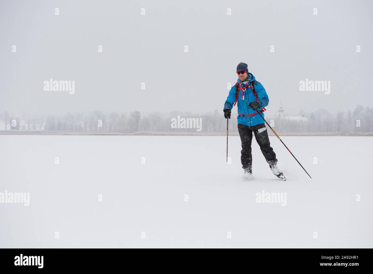 Man ice-skating on frozen lake Stock Photo