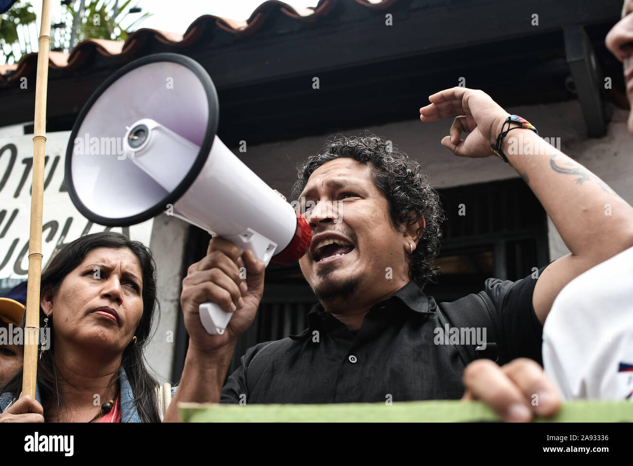 Supporter shouting on a megaphone during the protest.Supporters of social movements and Venezuelan communist youth protest in support of former president, Evo Morales in front of the Bolivian embassy. The president of the country resigned after strong protests against his re-election and for refusing to conduct an audit of votes. Stock Photo