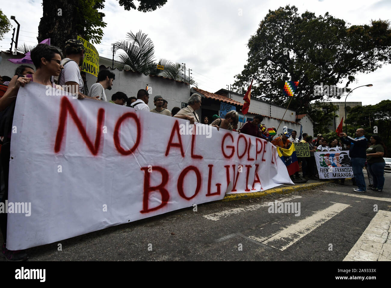 """A banner that reads """"Against the coup in Bolivia"""" during the protest.Supporters of social movements and Venezuelan communist youth protest in support of former president, Evo Morales in front of the Bolivian embassy. The president of the country resigned after strong protests against his re-election and for refusing to conduct an audit of votes. Stock Photo"""