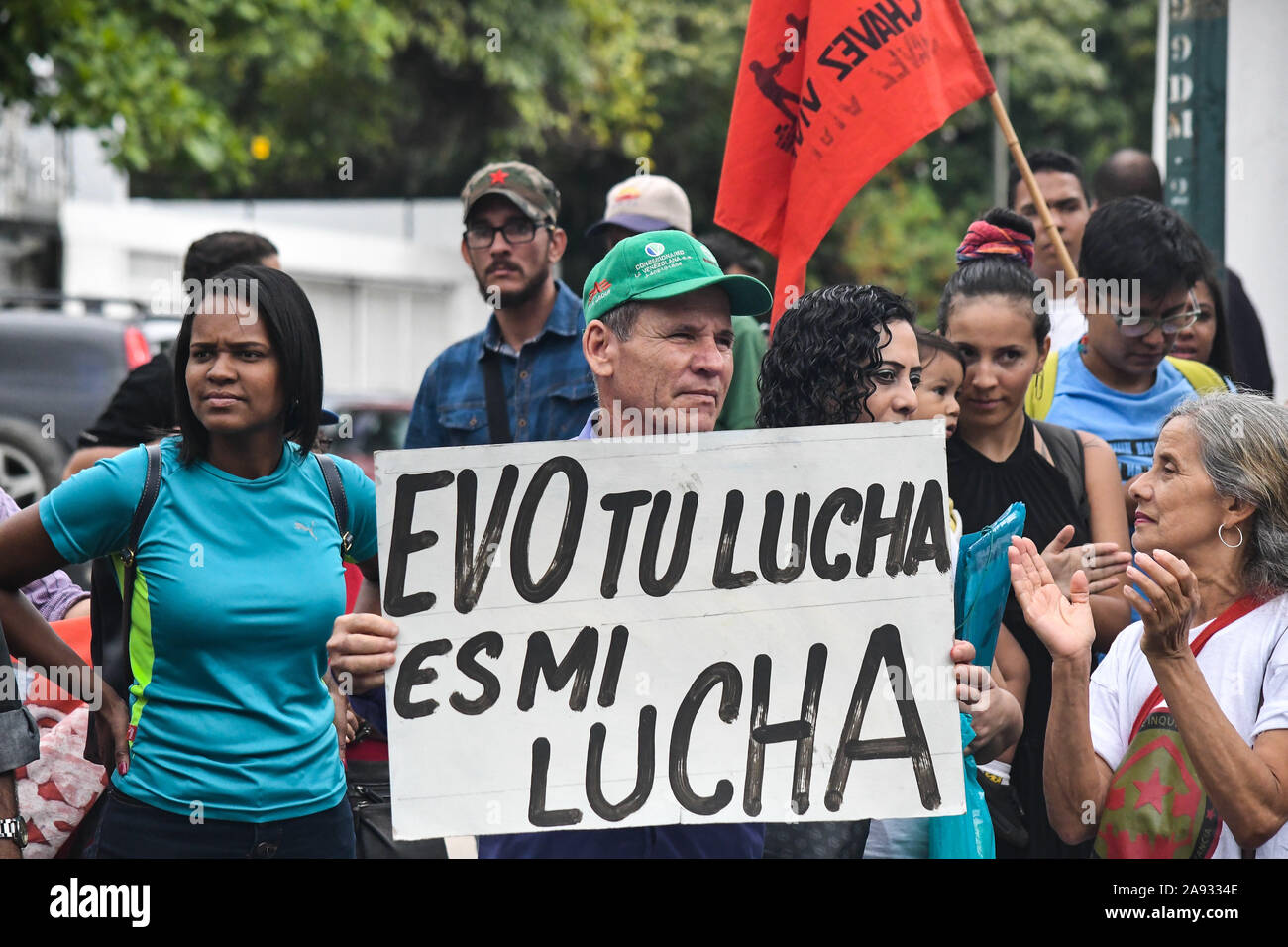 "A man holding a placard that reads ""Evo your fight is my fight"" during the protest.Supporters of social movements and Venezuelan communist youth protest in support of former president, Evo Morales in front of the Bolivian embassy. The president of the country resigned after strong protests against his re-election and for refusing to conduct an audit of votes. Stock Photo"