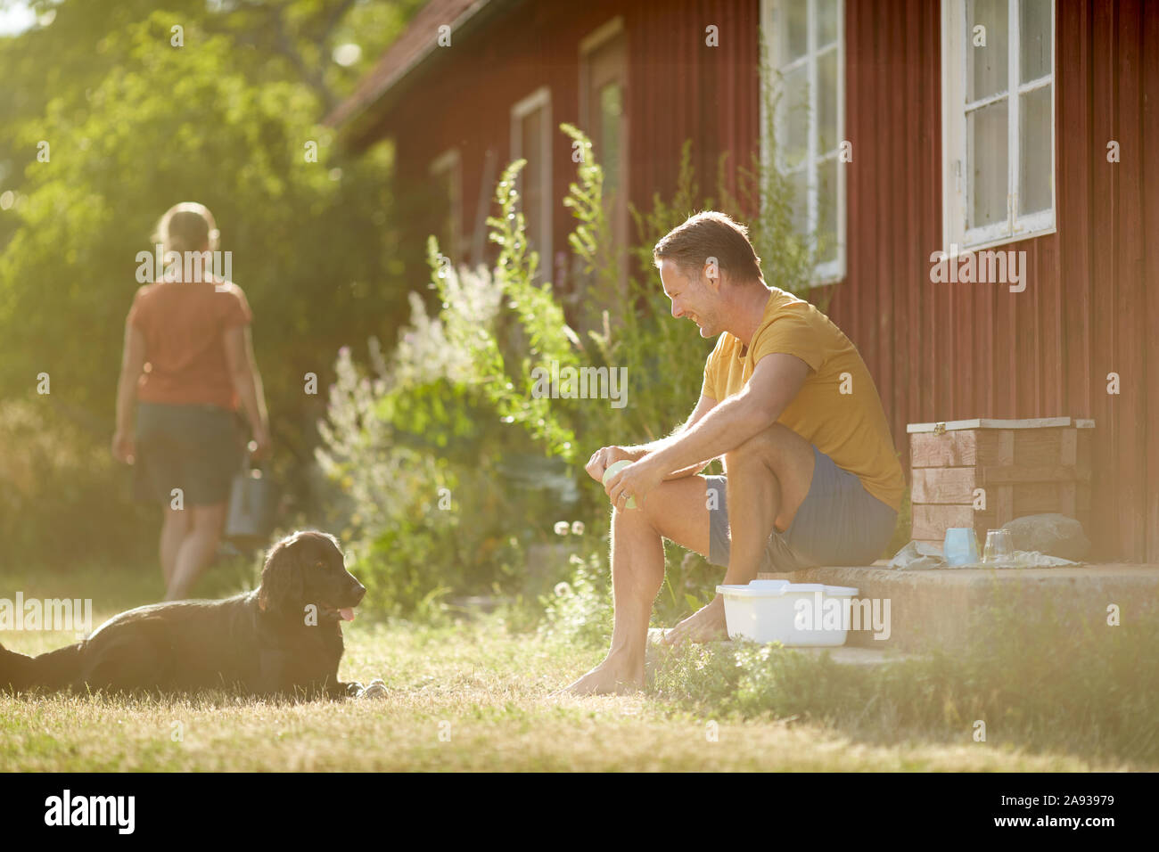 Man with dog in front of house Stock Photo