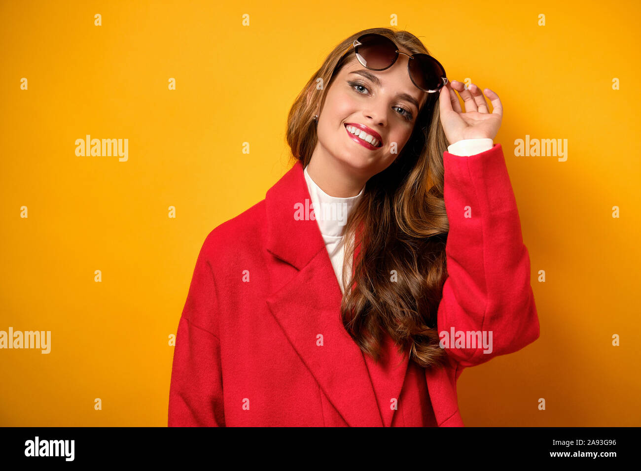 A beautiful girl with red lips stands in a red coat on a yellow background and looks up at the frame, lifting her sunglasses. Stock Photo