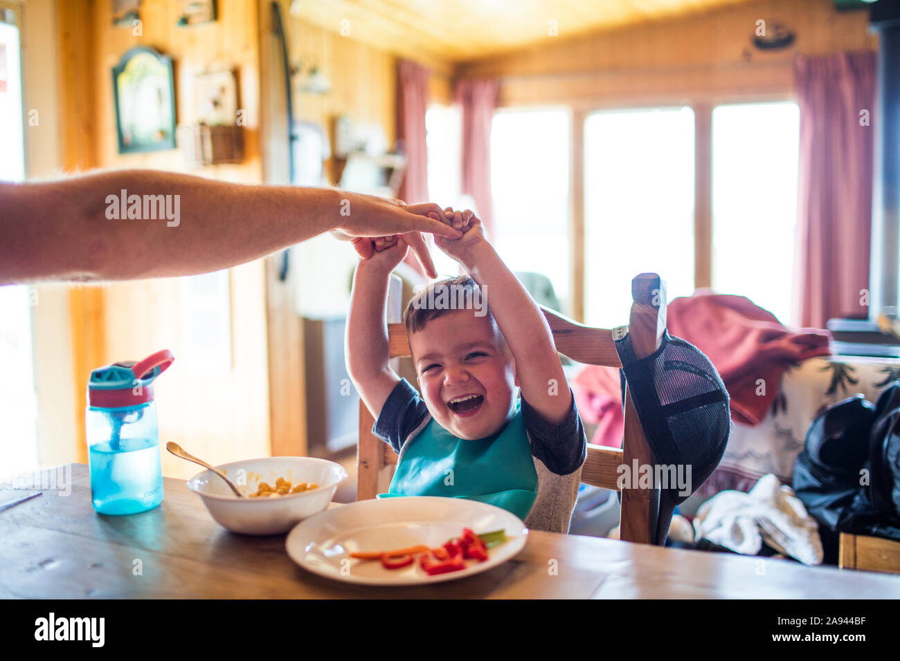 Father reach to tickle his son while at the table Stock Photo