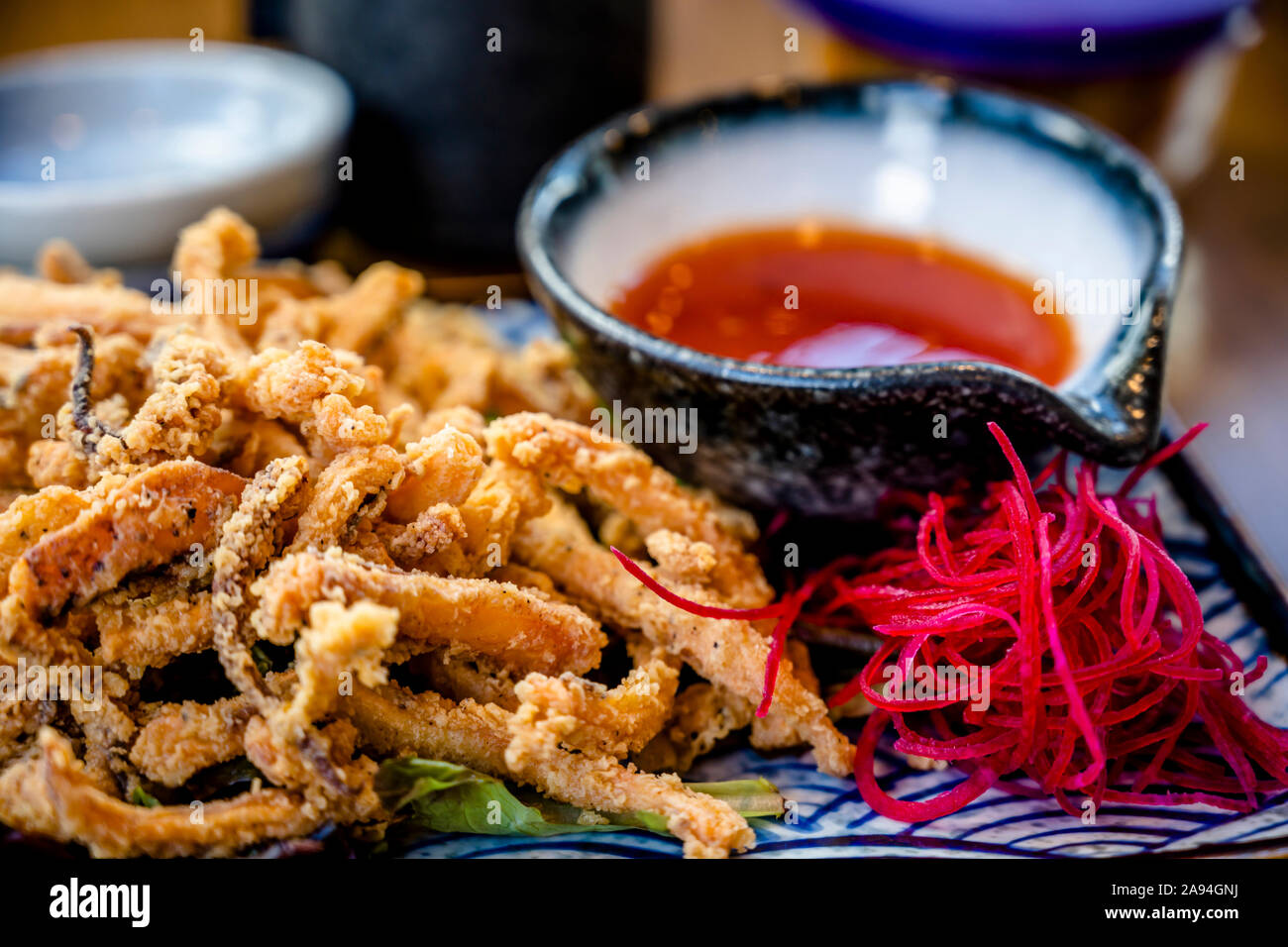 Plates with various kinds of expertly cooked fried squid with spices and hot sauces are displayed on dining table to enjoy delicious and dietary natur Stock Photo