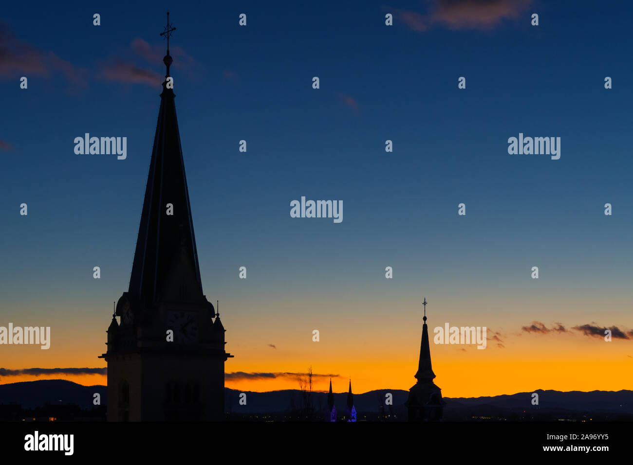 Cityscape silhouette of catholic church towers in Ljubljana on a wonderful orange blue evening sky background. Cityscapes and religion concepts. Stock Photo
