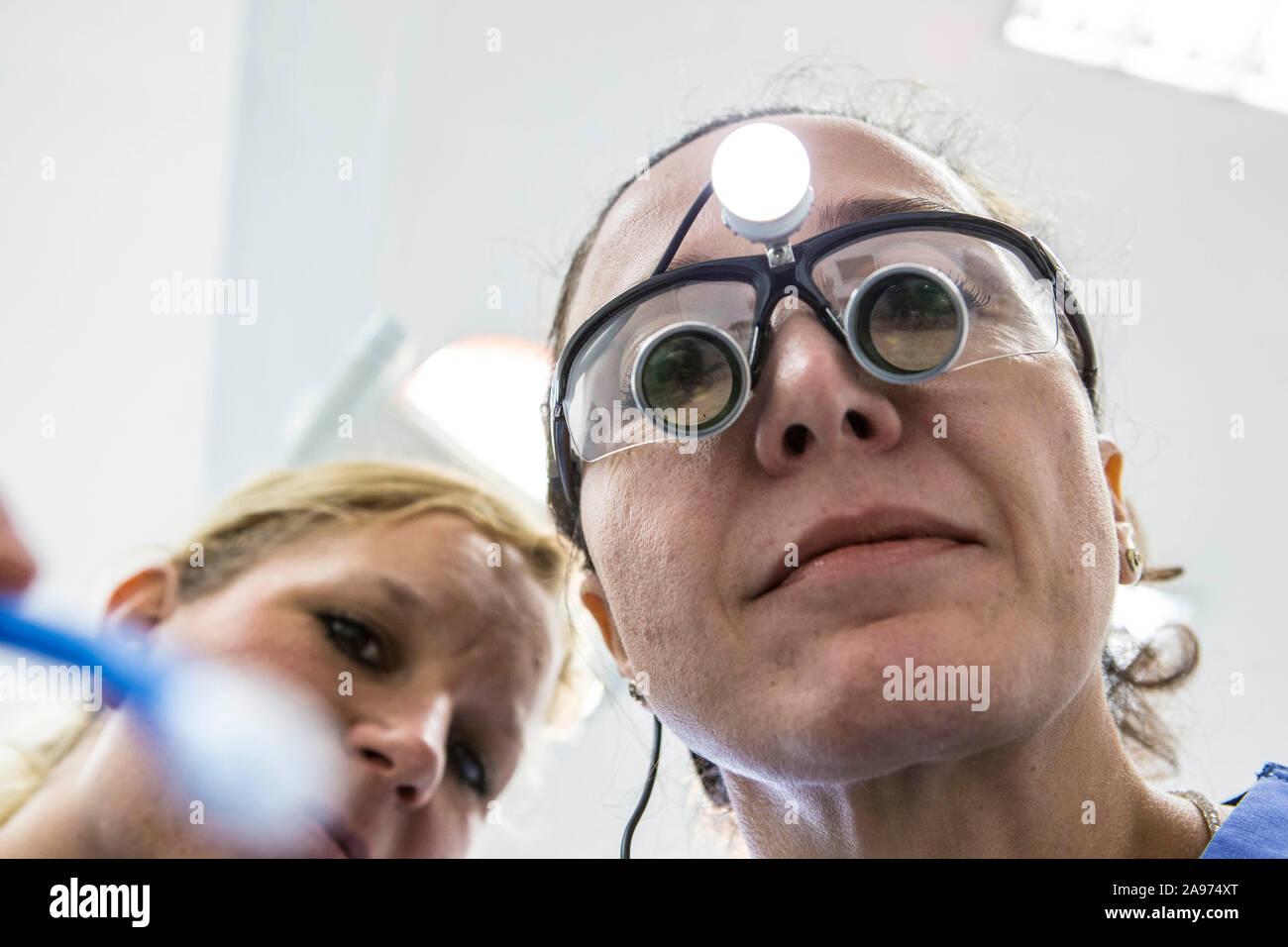 Eine Zahnärztin trägt bei der Behandlung ihrer Patienten eine Lupenbrile. Diese beleuchtete Spezialbrille hat eine Schutzwirkung gegen Splitter beim B Stock Photo