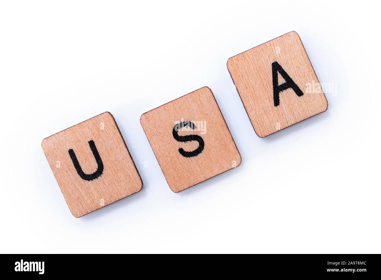 The abbreviation USA - standing for the United States of America, spelt with wooden letter tiles over a white background. Stock Photo