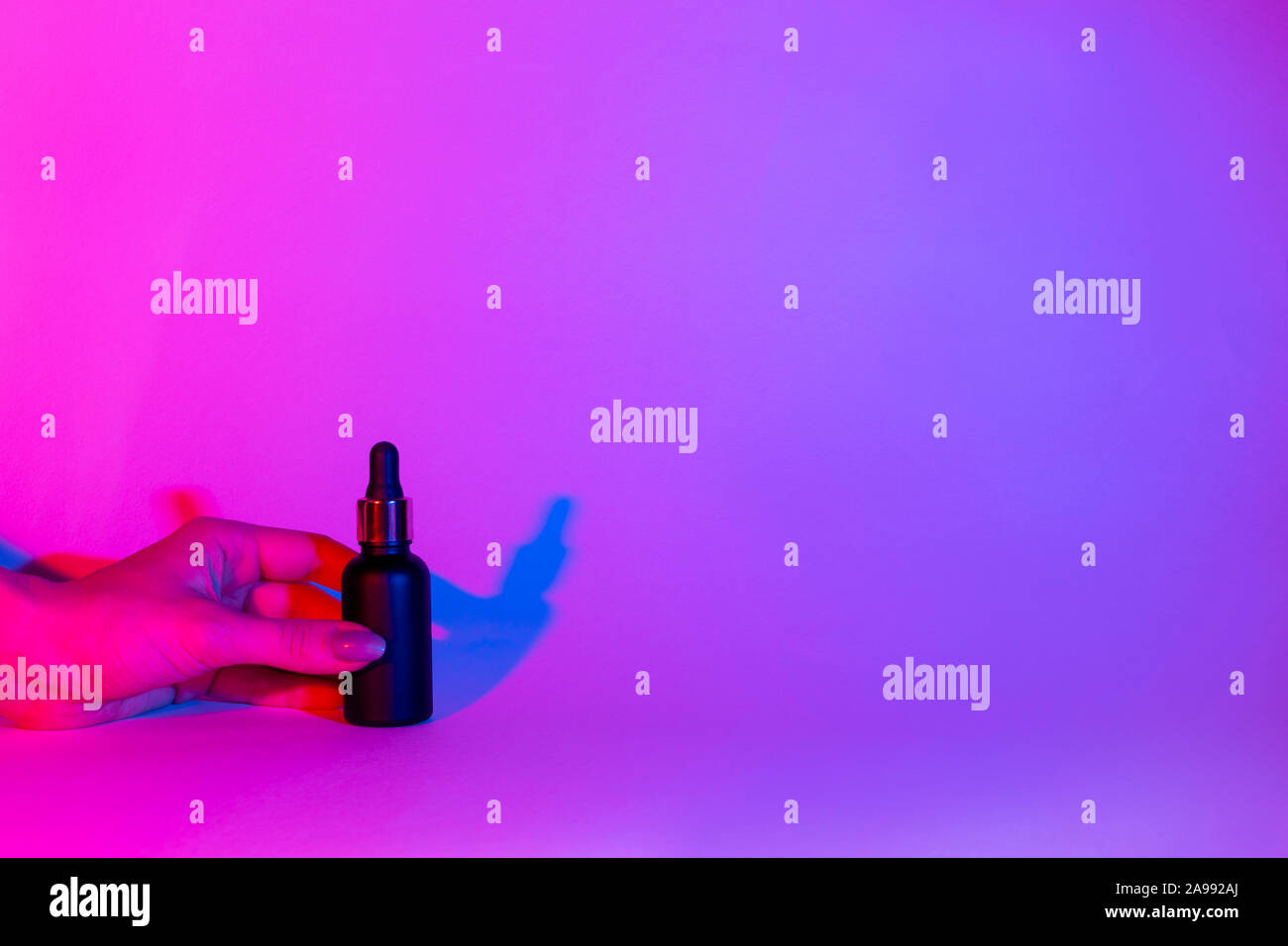 Female hand holds a bottle of black matte color on a neon trend background. Cosmetics concept. glass bottle mockup. Stock Photo