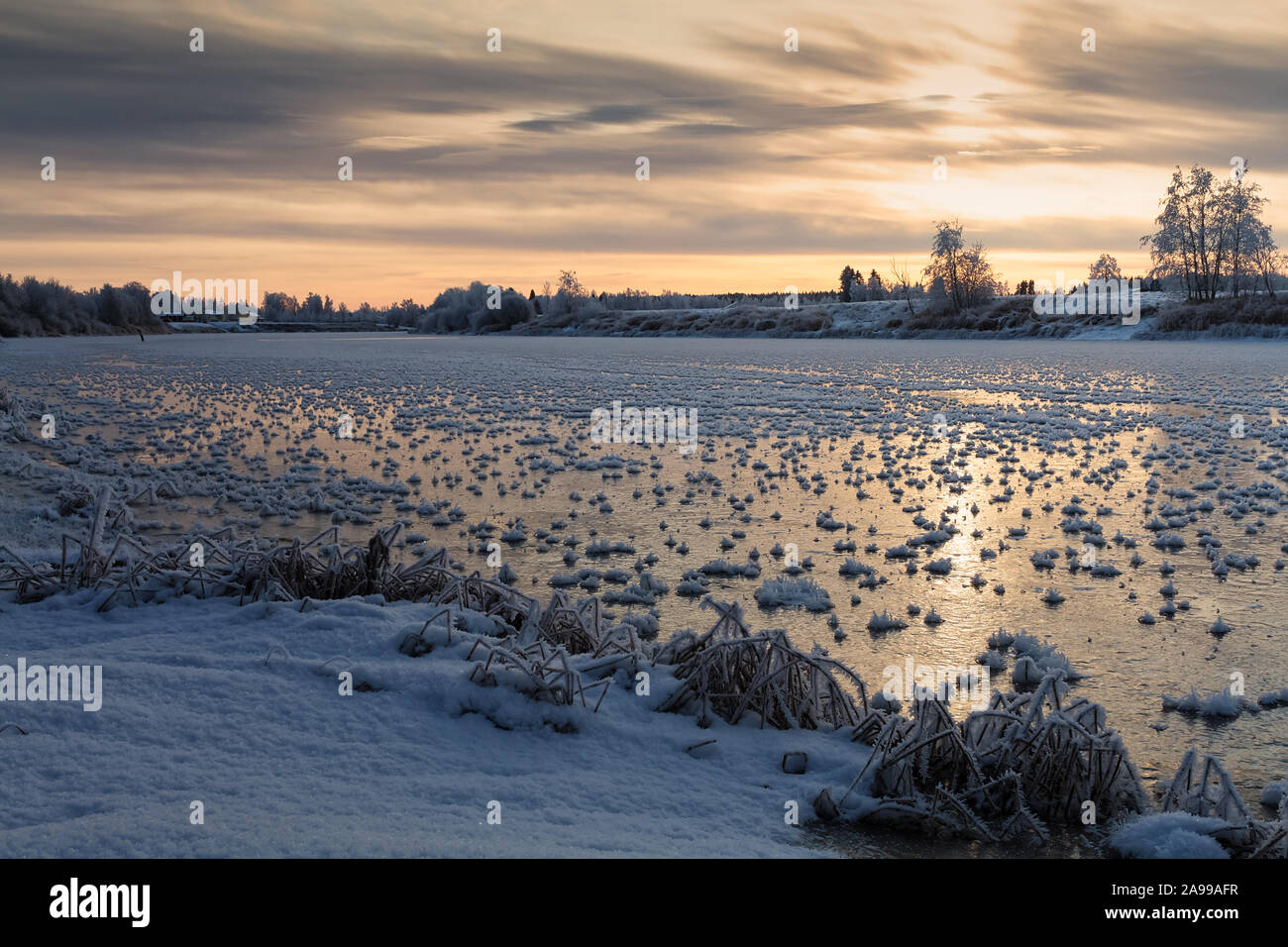 The winter sun rises over the freezing river at the Northern Finland. The river surface is covered with spiked frost formations. Stock Photo