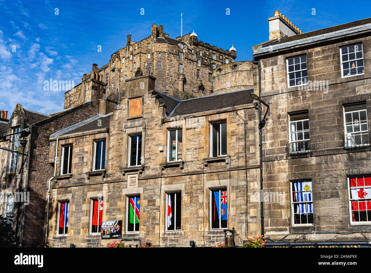 Close up Detail of Historic Buildings in the Grassmarket With View of Edinburgh Castle Towering Above with a Blue Sky #2. Edinburgh, Scotland. Stock Photo