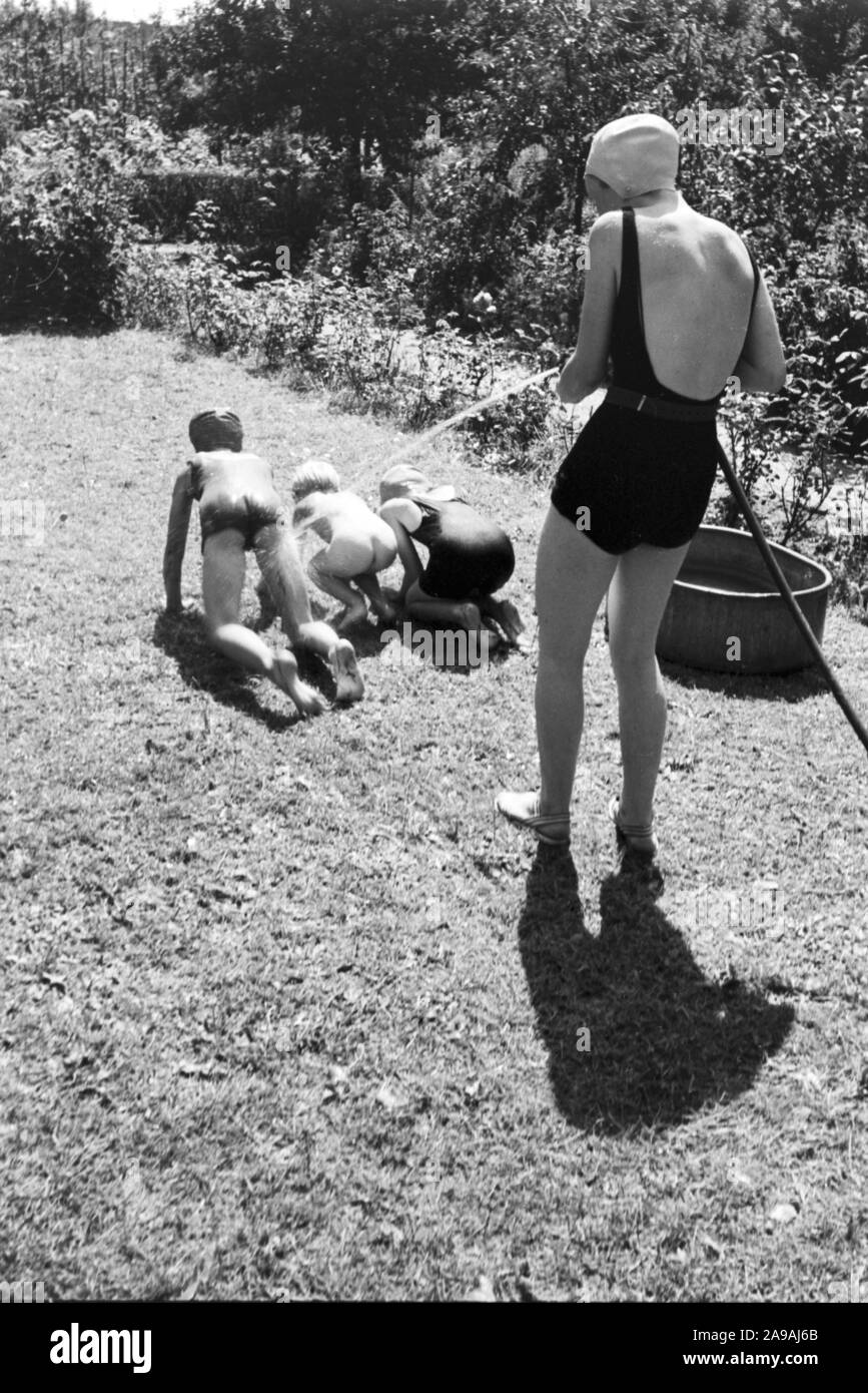 A family in their garden, Germany 1930s. Stock Photo