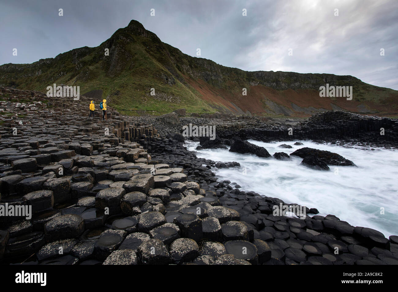 Mother and son standing on pile of rock columns formation at Giant's Causeway, Co. Antrim, Northern Ireland Stock Photo