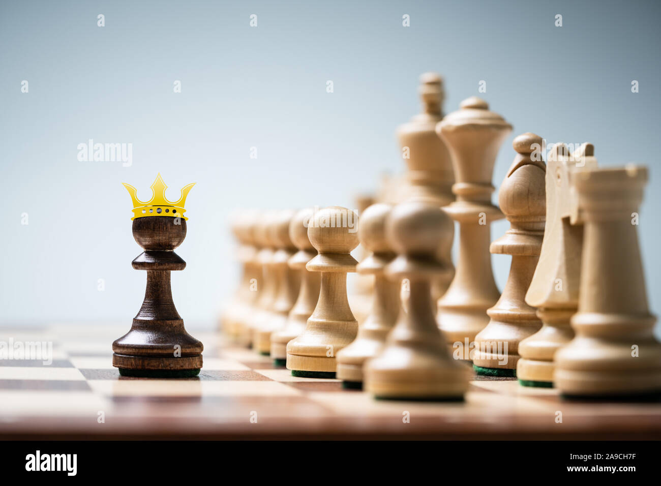 Row Of Chess Pieces On Board Against Blue Background Stock Photo