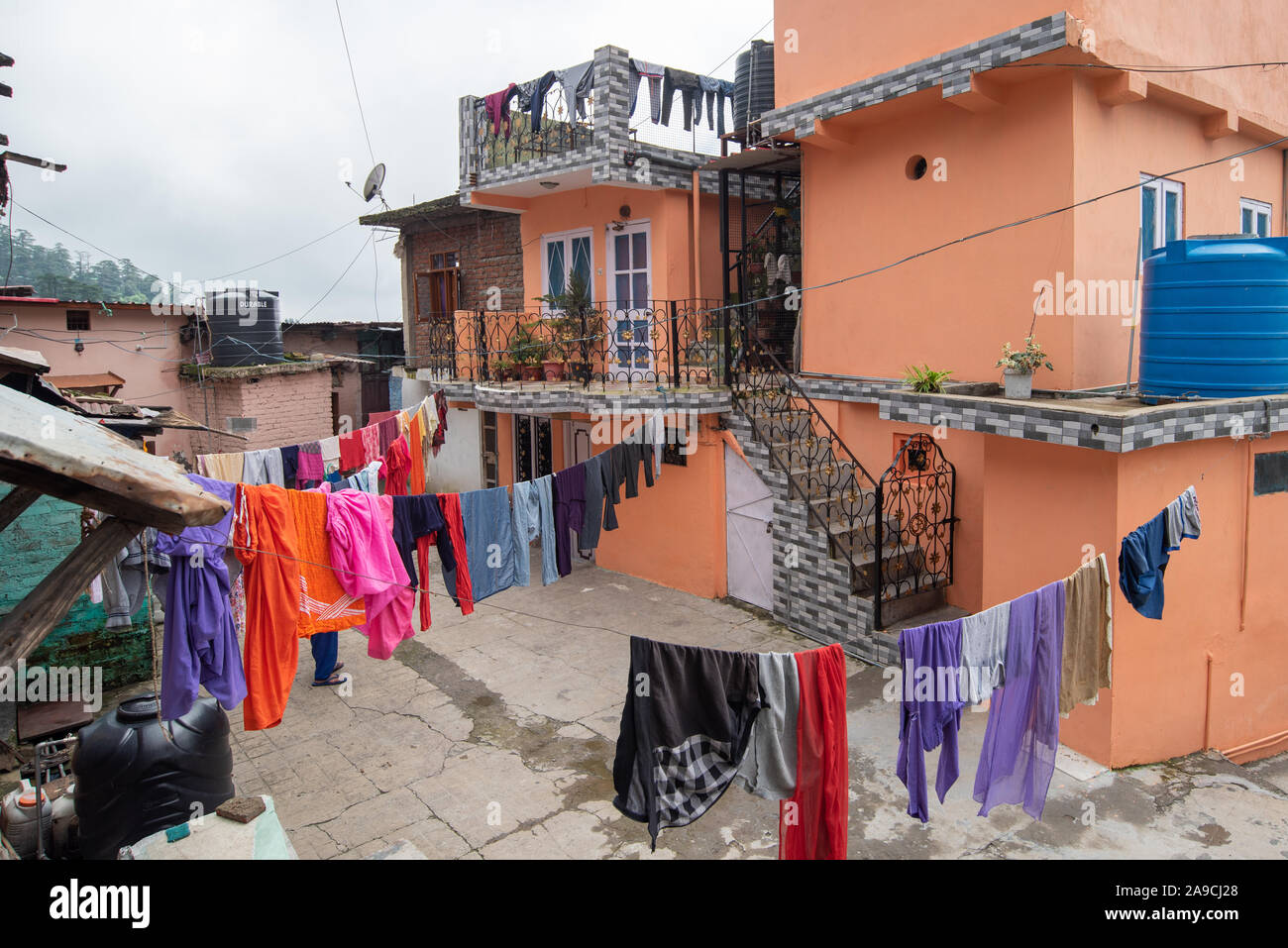 View of houses hugging the hillside in Shimla constructed close to each other. In the foreground clothes are being dried Stock Photo