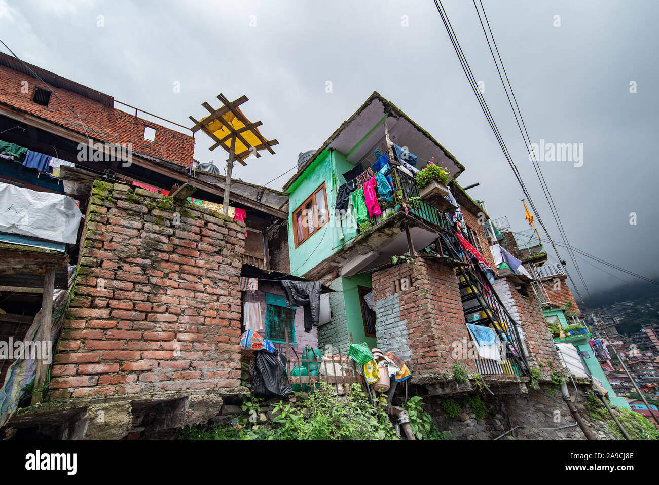 Houses in Shimla where the focus is on a makeshift contraption which forms a perch for pigeons in this hillside colony Stock Photo
