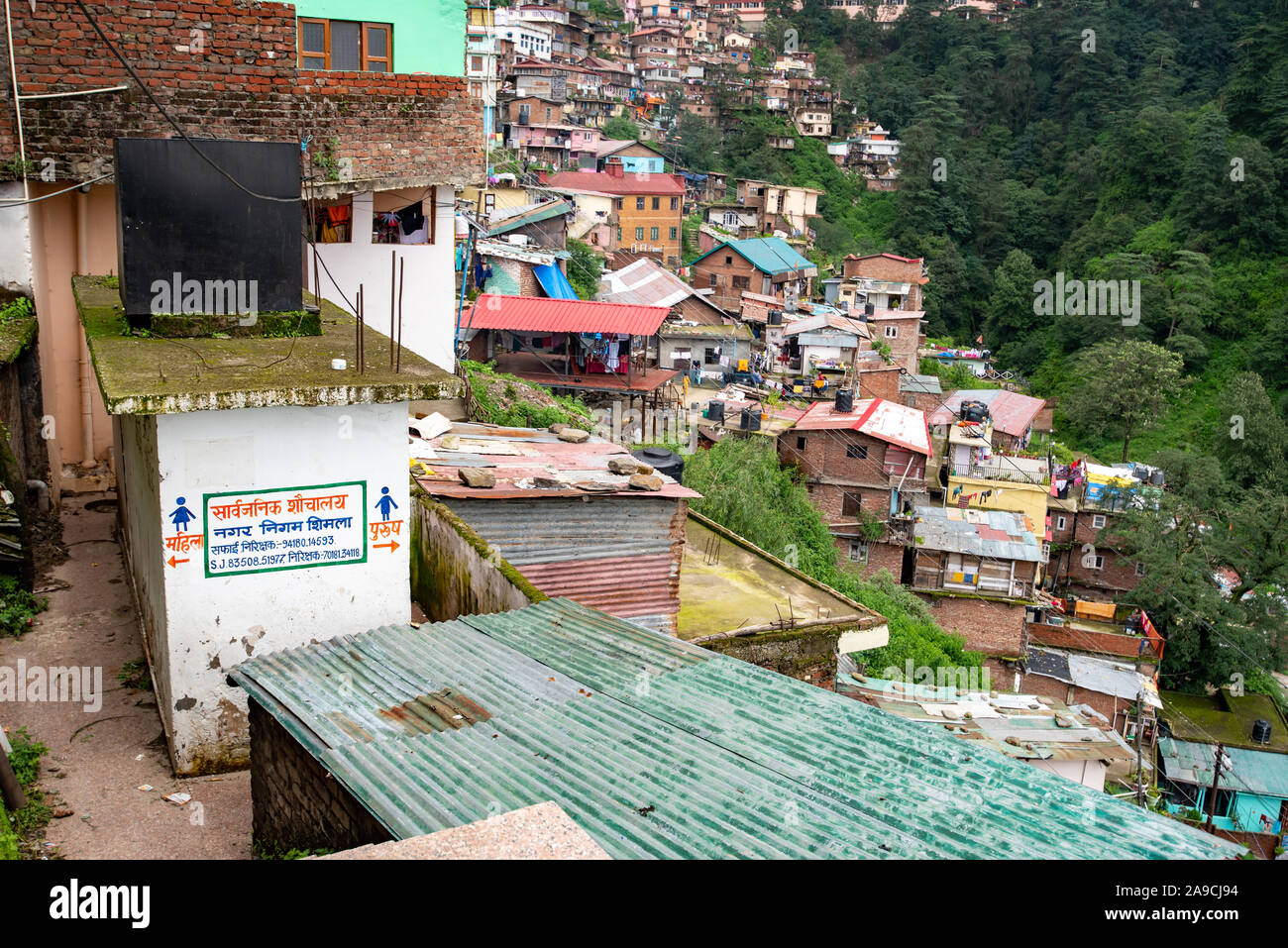 Houses in Shimla hug the steep hilly slopes Stock Photo