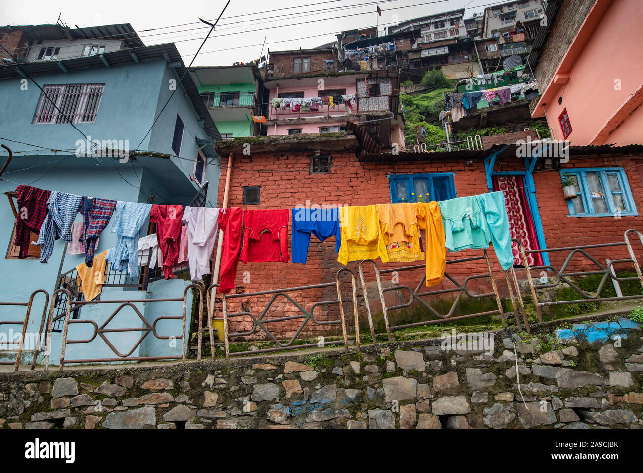 View of houses hugging the hillside in Shimla are constructed close to each other. In the foreground clothes are being dried Stock Photo