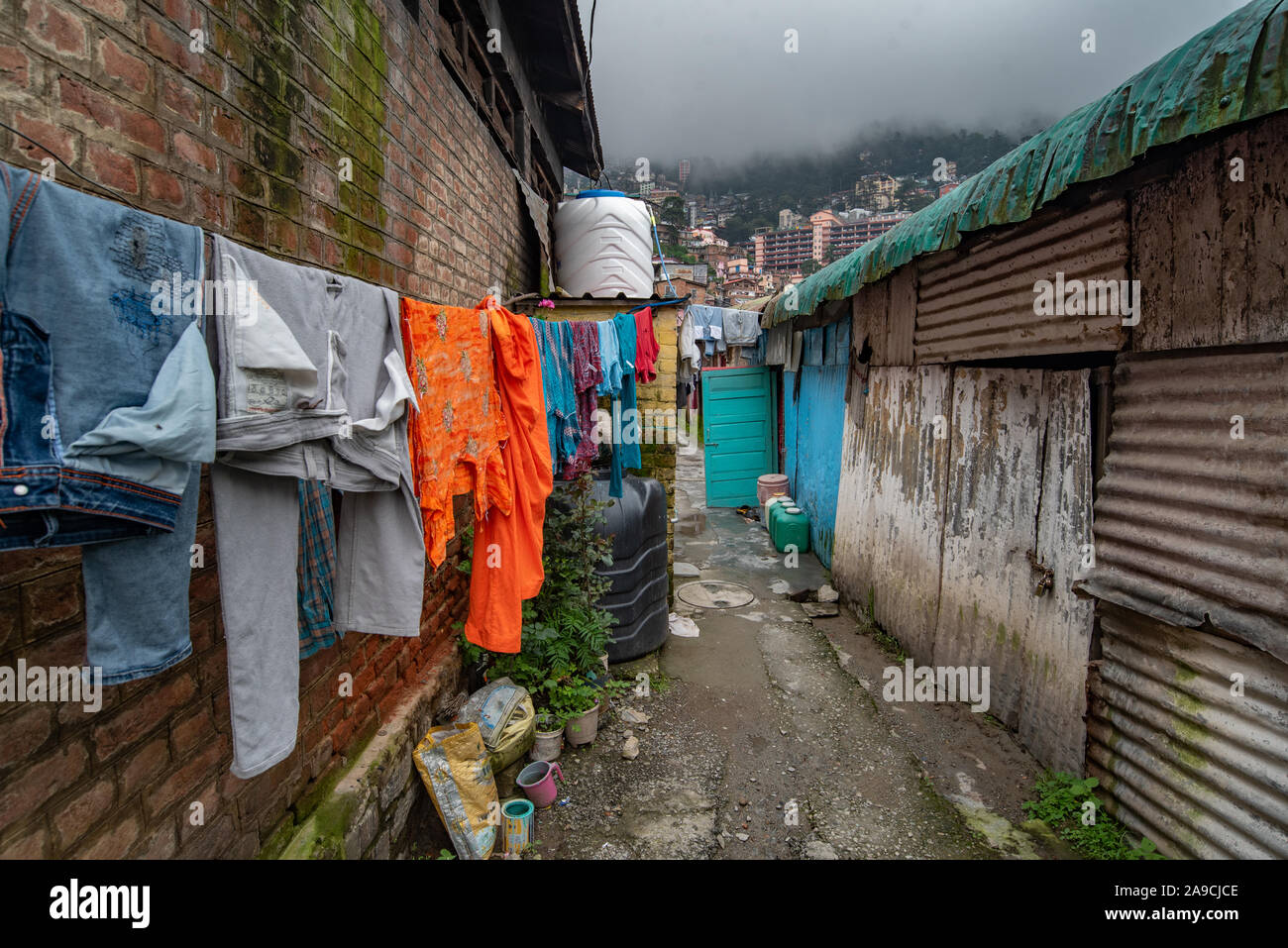 View of a street in Shimla showing clothes drying and water containers outside homes amidst heavy monsoons and water shortage Stock Photo
