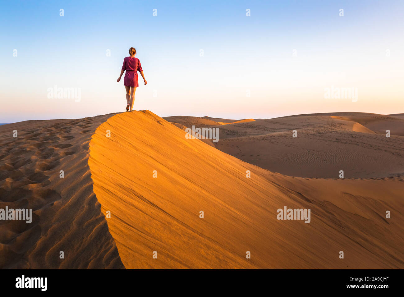 Girl walking on sand dunes in arid desert at sunset and wearing dress, scenic landscape of Sahara or Middle East Stock Photo