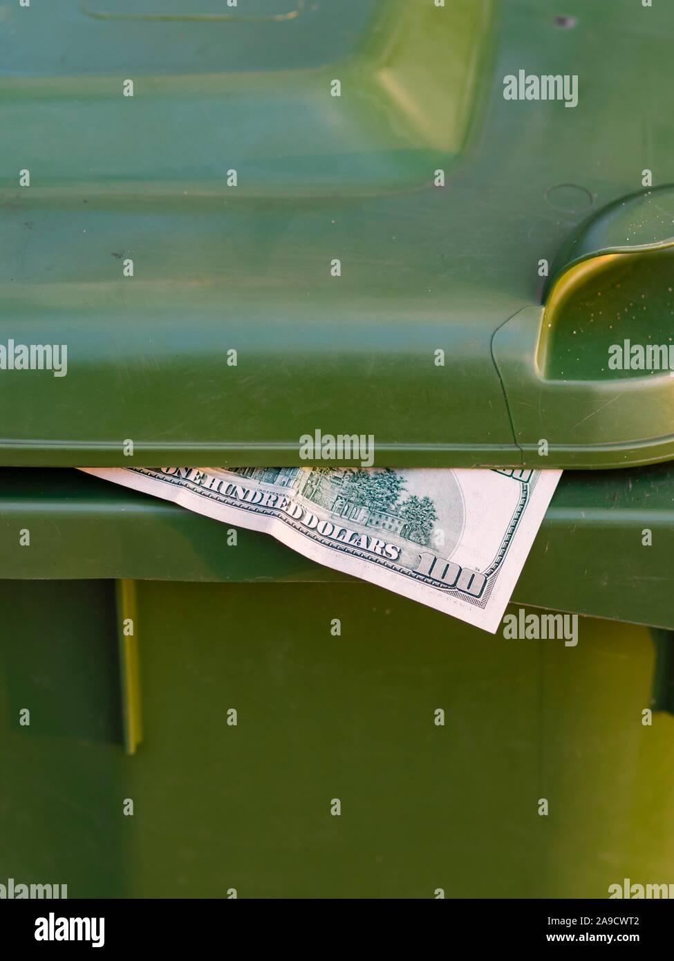 Money in trash bin Stock Photo