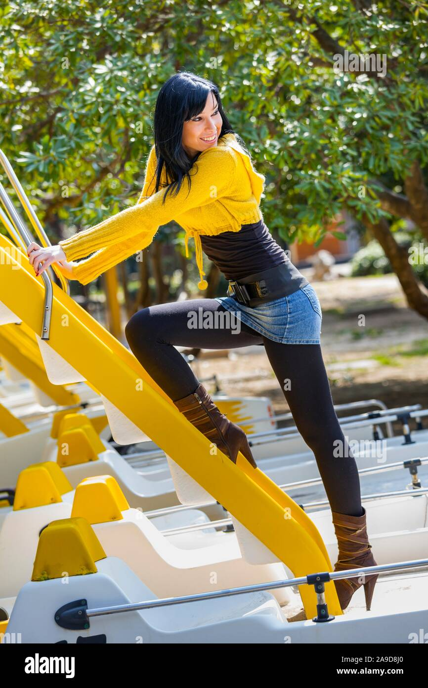 Beautiful teen girl in Yellow looking back over shoulder climbing ladder steps Stock Photo