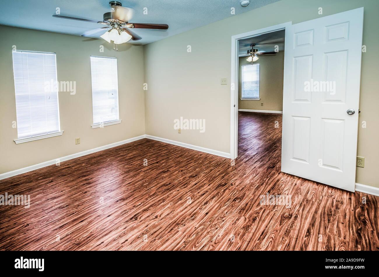 Empty bedrooms feature hardwood floors and lots of window ...