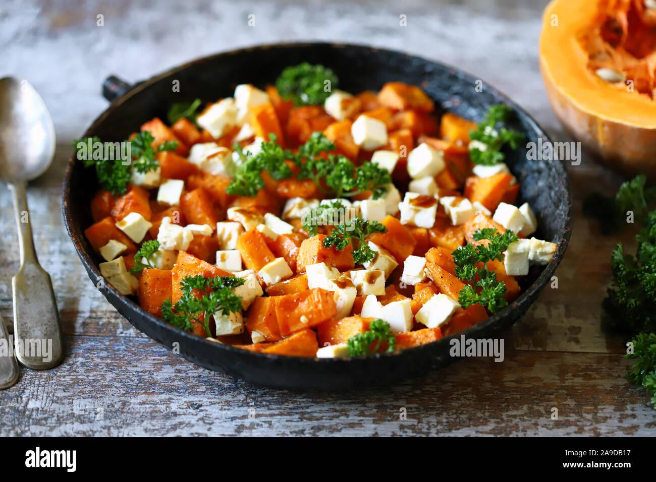 Salad with baked pumpkin and feta. Thanksgiving salad. Autumn keto salad. Keto diet. Selective focus. Macro. Stock Photo
