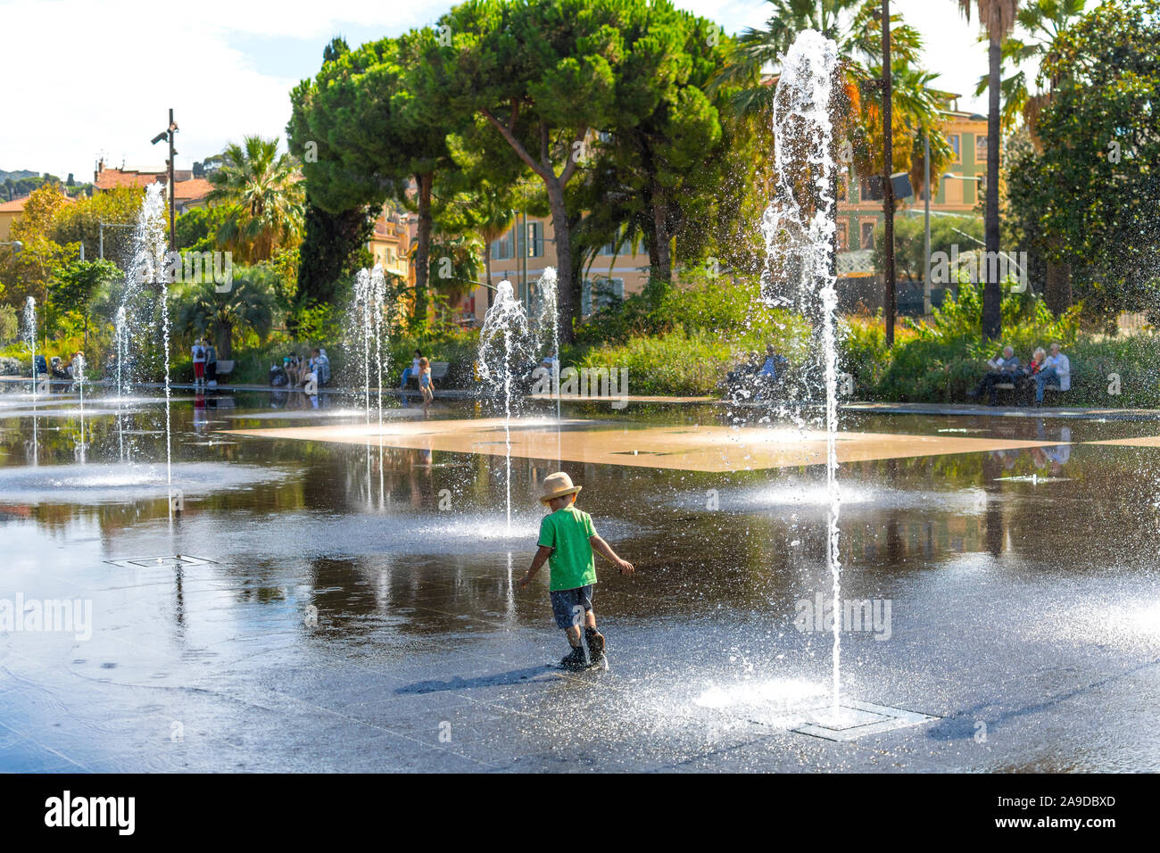 A young boy with a hat plays and splashes in the Promenade du Paillon Park in the touristic old town area of Nice, France on the French Riviera. Stock Photo