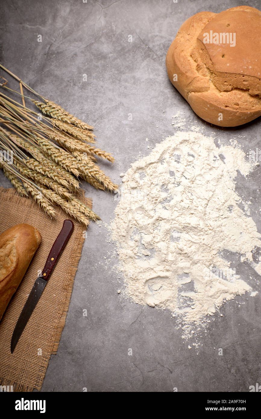 Rustic bread and wheat spikes on a grey background - Healthy food concept Stock Photo