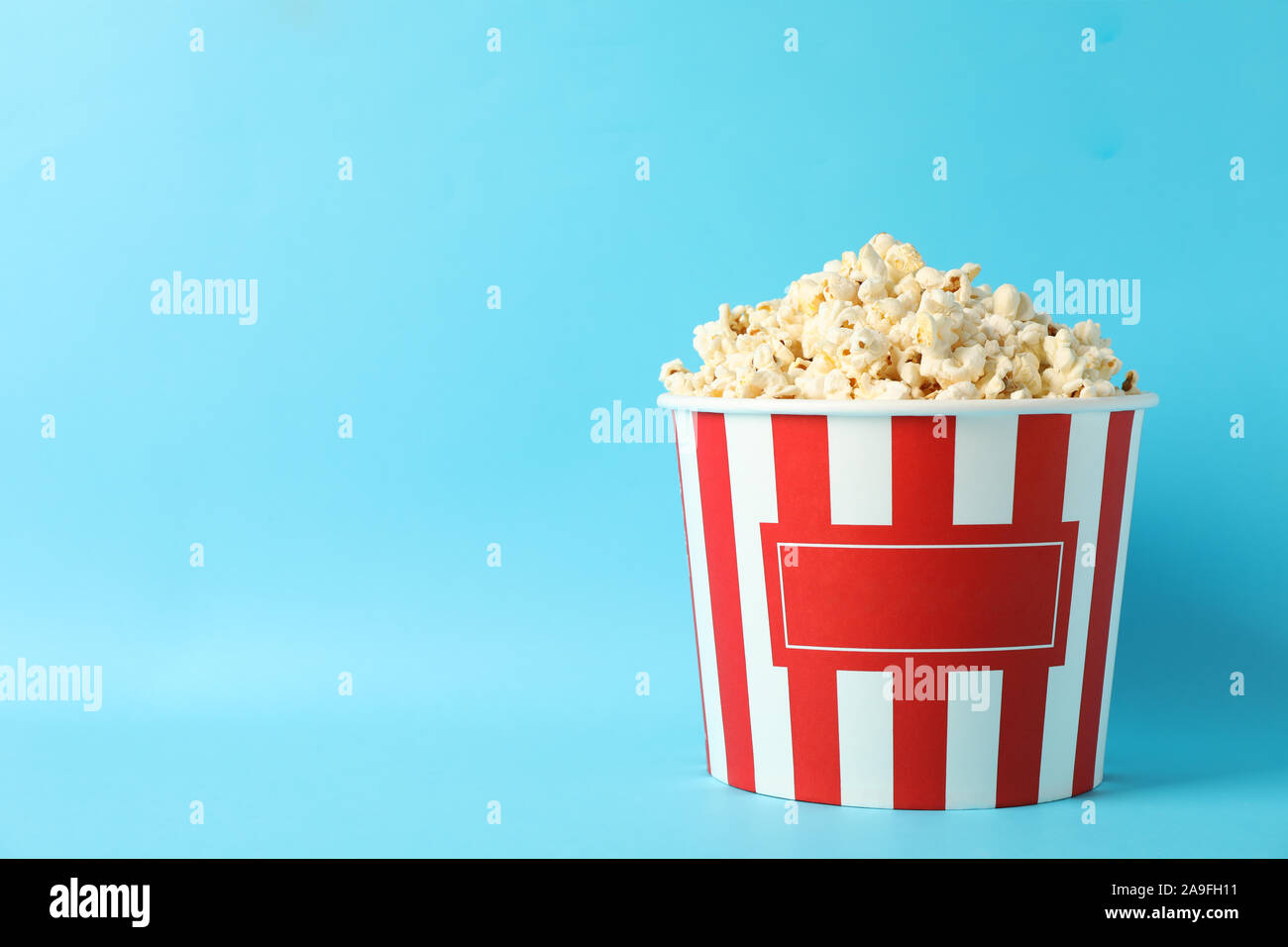 Striped Bucket With Popcorn On Blue Background Space For Text Stock Photo Alamy