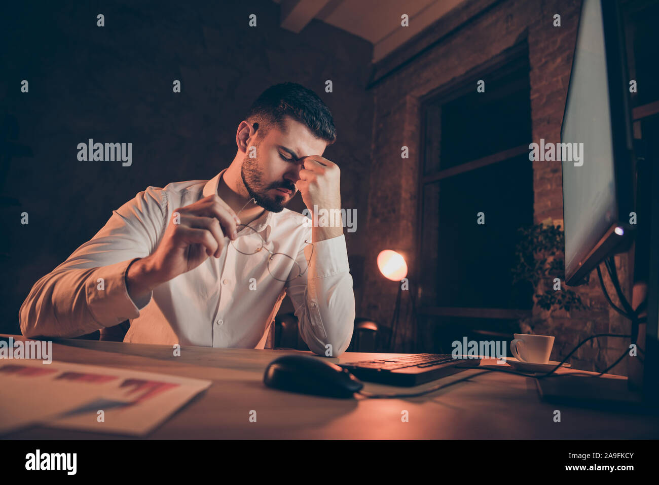 Low below angle view photo of tired businessman with head hurting migraine eyes aching putting glasses off sitting at desktop Stock Photo