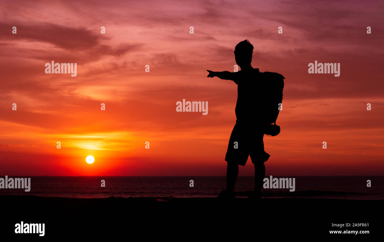Man on the sunset after help baby turttles go to the ocean Stock Photo