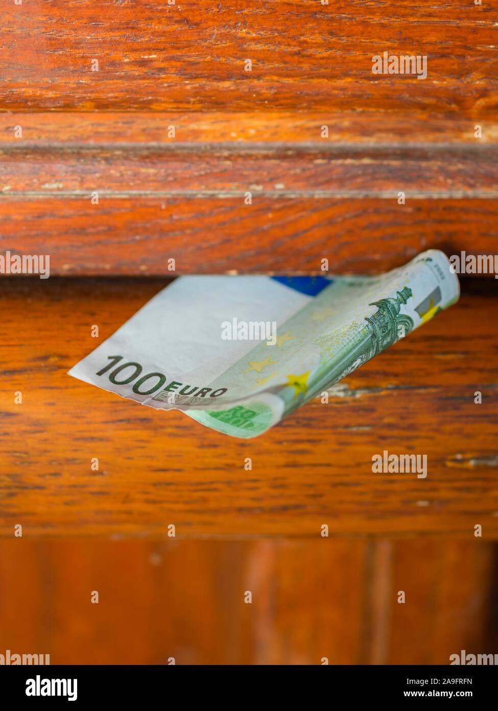 Money attached to wooden slit enclosure cover Stock Photo