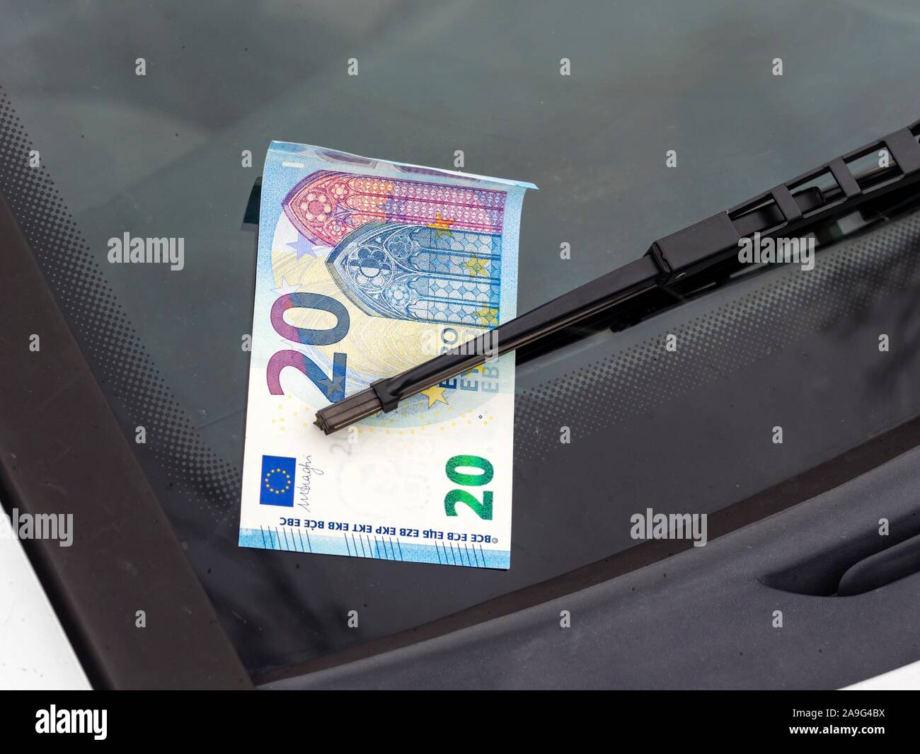 Lost and found money attached under car windshield rain wiper Stock Photo