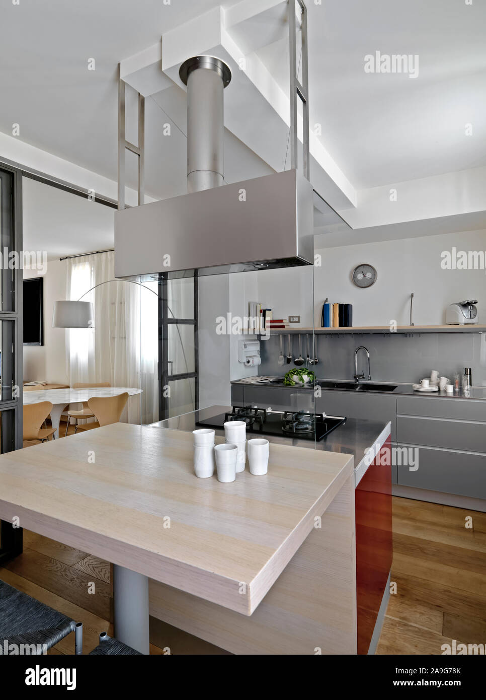 Interior Shot Of A Modern Kitchen In Foreground The Kitchen Island With Wood Dining Table And Gas Hob While On Background The Kitchen Cabinets With Bu Stock Photo Alamy