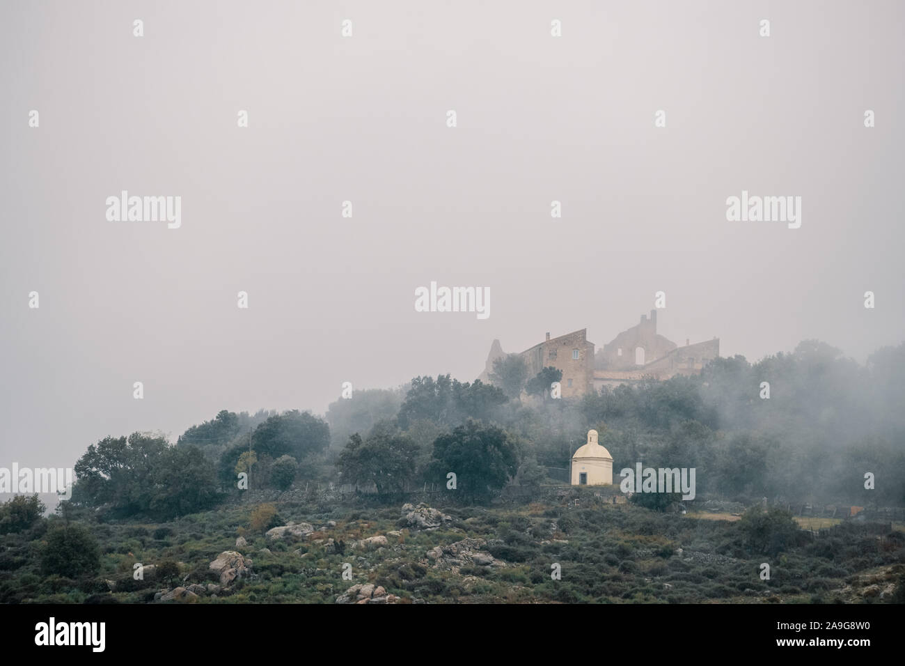 The ancient Couvent Santa Maria di a Pace and a mausoleum shrouded in mist in the ancient mountain village of Speloncato in the Balagne region of Cors Stock Photo