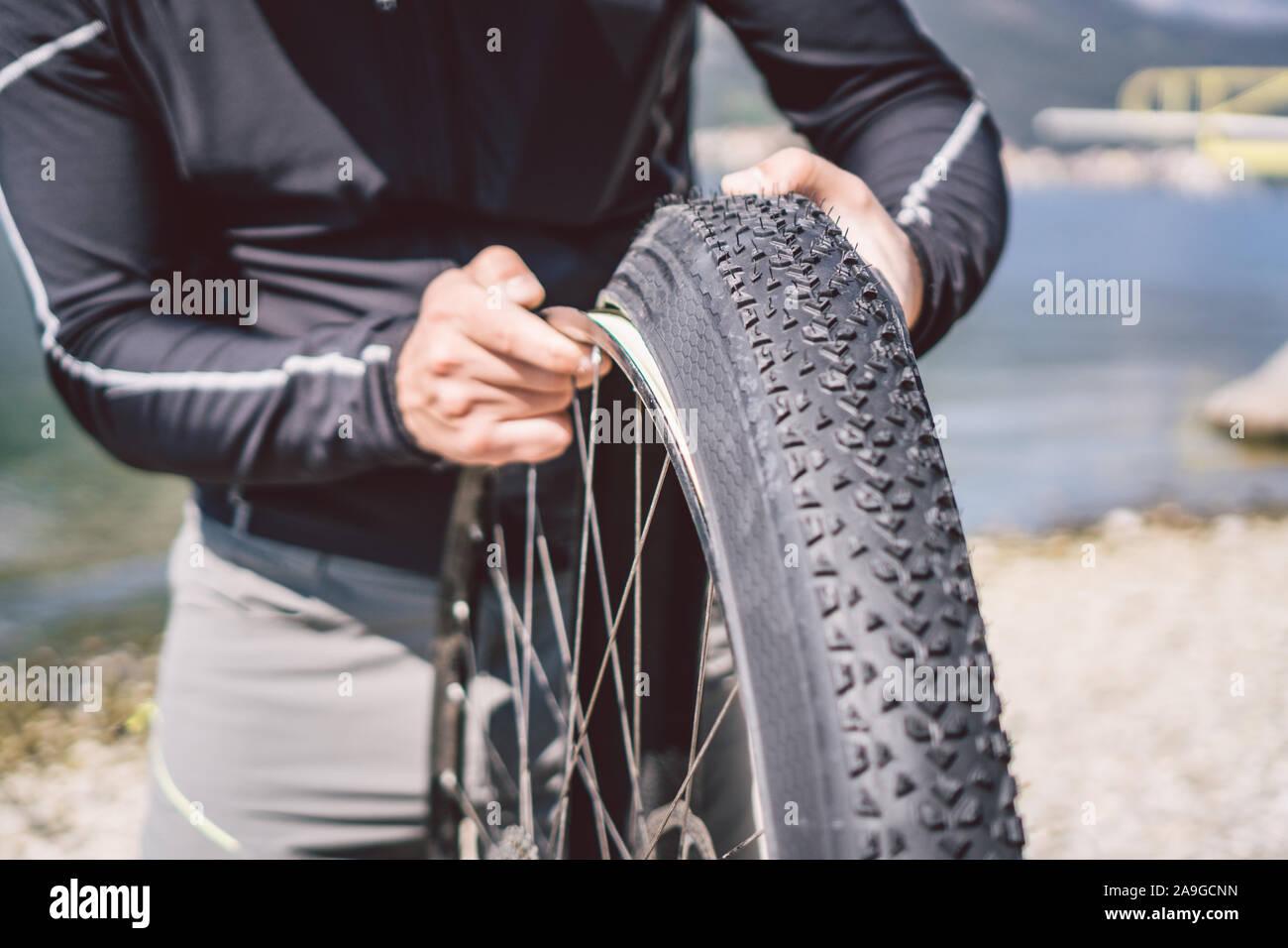 Bike Repair. Man Repairing Mountain Bike. Cyclist man in trouble rear wheel wheel case of accident. Man Fixes Bike near lake in Italy background Stock Photo