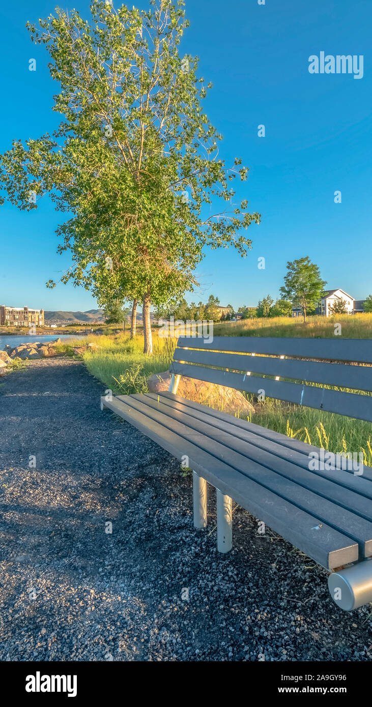 Vertical Bench at the shore of a lake with homes and buildings background on a sunny day Stock Photo