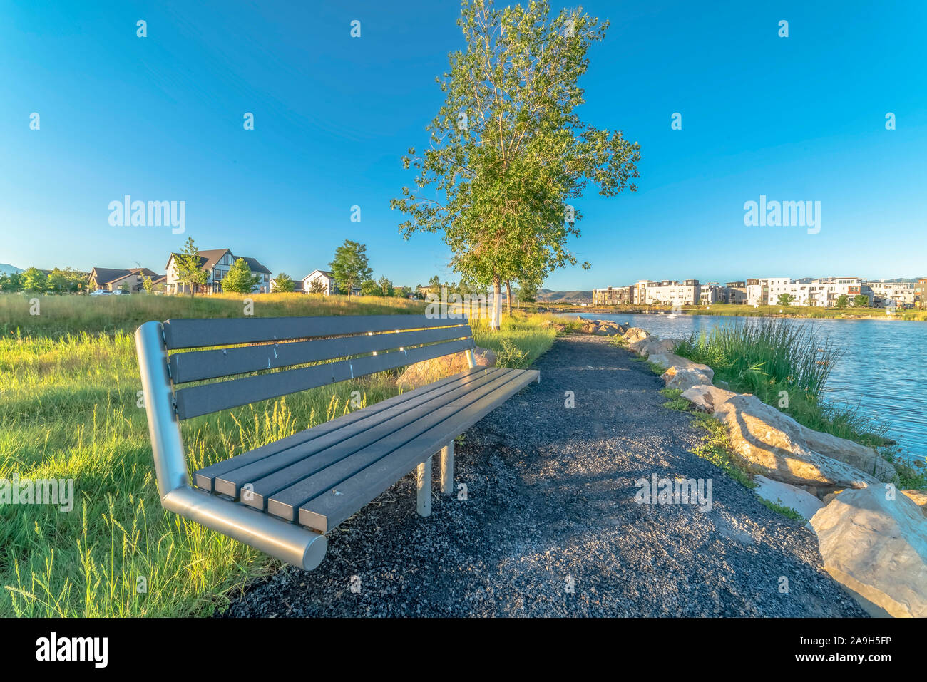 Bench at the shore of a lake with homes and buildings background on a sunny day Stock Photo