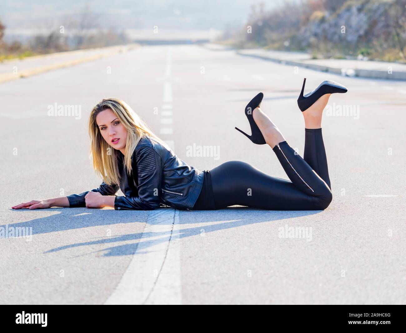 Young woman legs heels lying on asphalt ground tummy stomach legs raising raise in air upwards Stock Photo