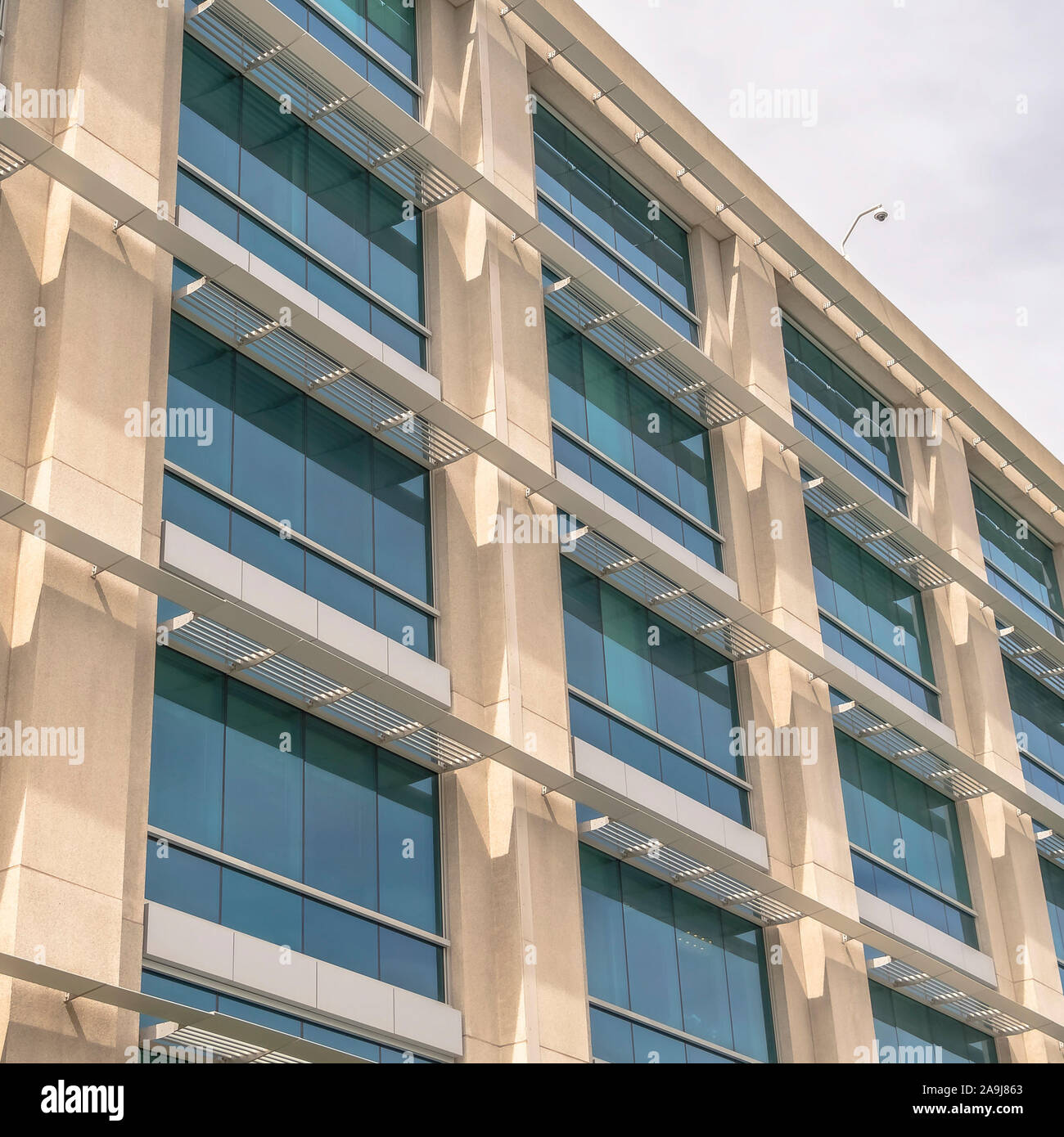 Square frame Modern building facade close up with glass windows and sunlit concrete wall Stock Photo